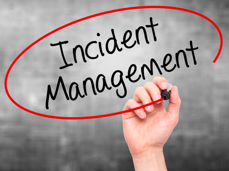 drp: Man Hand writing Incident Management with black marker on visual screen. Isolated on grey. Business, technology, internet concept. Stock Photo