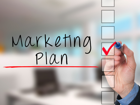 Business Man Hand Writing Marketing Plan Concept And Ticking Stock