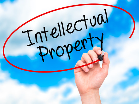 lawer: Man Hand writing Intellectual Property with black marker on visual screen. Isolated on sky. Business, technology, internet concept. Stock Photo Stock Photo