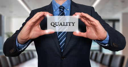 sell shares: Businessman holding Quality sign. Office - Stock Photo