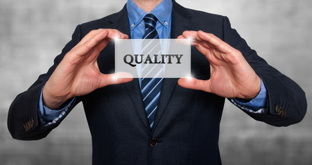 sell shares: Businessman holding Quality sign. Grey- Stock Photo