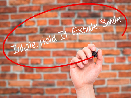 to inhale: Man Hand writing Inhale Hold It Exhale Smile with black marker on visual screen. Isolated on bricks. Business, technology, internet concept. Stock Photo