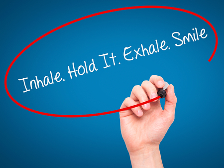 exhale: Man Hand writing Inhale Hold It Exhale Smile with black marker on visual screen. Isolated on blue. Business, technology, internet concept. Stock Photo Stock Photo