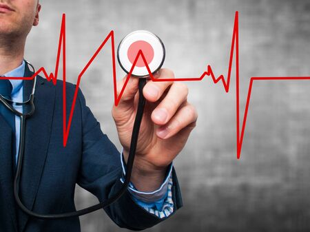 preventive medicine: Closeup portrait handsome business man, male corporate employee, worker listening to  heart beat with stethoscope isolated on grey background. Preventive medicine, financial condition concept