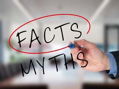 exactitude: Businessman hand drawing and choosing Facts instead of Myths. Facts selected with marker. Isolated on office background. Stock Image