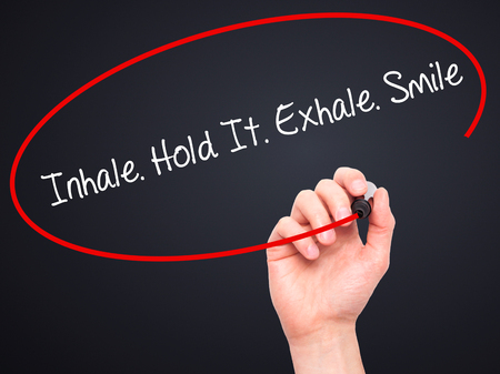 exhale: Man Hand writing Inhale Hold It Exhale Smile with black marker on visual screen. Isolated on black. Business, technology, internet concept. Stock Photo