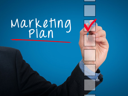 stock listing: Businessman hand writing Marketing Plan and check listing task. Isolated on blue background. Stock photo