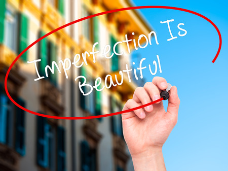 self conceit: Man Hand writing Imperfection Is Beautiful with black marker on visual screen. Isolated on background. Business, technology, internet concept. Stock Photo
