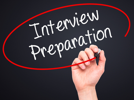 job qualifications: Man Hand writing Interview Preparation with black marker on visual screen. Isolated on black. Business, technology, internet concept. Stock Photo