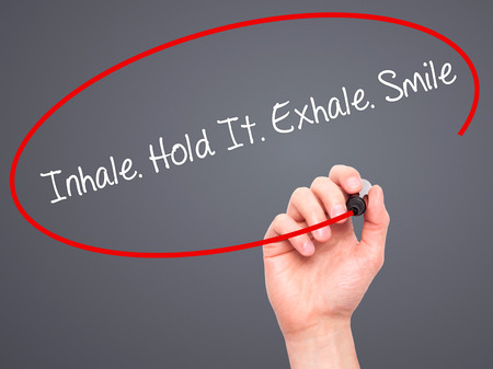 exhale: Man Hand writing Inhale Hold It Exhale Smile with black marker on visual screen. Isolated on grey. Business, technology, internet concept. Stock Photo Stock Photo