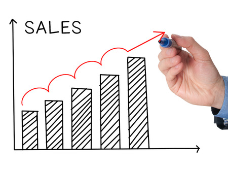 sales growth: Businessman hand drawing Sales Growth Graph with marker on transparent wipe board. Isolated on white. Sales concept. Stock Image