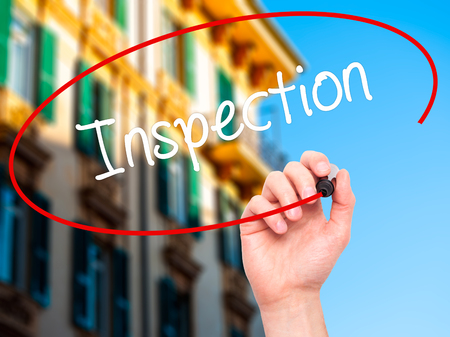 warranty questions: Man Hand writing Inspection with black marker on visual screen. Isolated on city. Business, technology, internet concept. Stock Photo Stock Photo