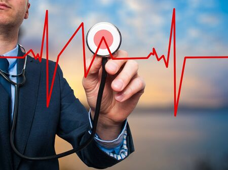 preventive medicine: Closeup portrait handsome business man, male corporate employee, worker listening to  heart beat with stethoscope isolated on nature background. Preventive medicine, financial condition concept