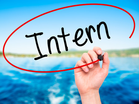 intern: Man Hand writing Intern  with black marker on visual screen. Isolated on background. Business, technology, internet concept. Stock Photo