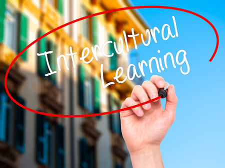 intercultural: Man Hand writing Intercultural Learning with black marker on visual screen. Isolated on city. Business, technology, internet concept. Stock Photo