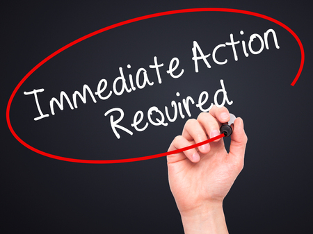 immediate: Man Hand writing Immediate Action Required with black marker on visual screen. Isolated on black. Business, technology, internet concept. Stock Photo