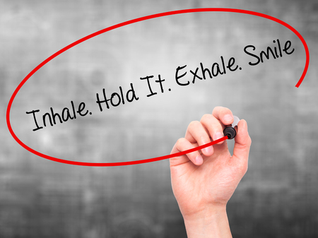 to inhale: Man Hand writing Inhale Hold It Exhale Smile with black marker on visual screen. Isolated on grey. Business, technology, internet concept. Stock Photo Stock Photo