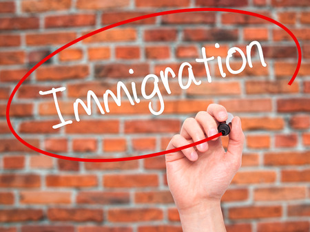 visa approved: Man Hand writing Immigration with black marker on visual screen. Isolated on bricks. Business, technology, internet concept. Stock Photo Stock Photo