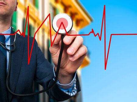 preventive medicine: Closeup portrait handsome business man, male corporate employee, worker listening to  heart beat with stethoscope isolated on city background. Preventive medicine, financial condition concept Stock Photo