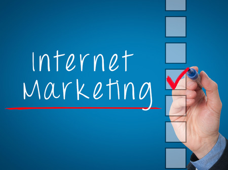 stock listing: Business hand writing internet marketing and check listing task concept. Isolated on blue background. Stock Image Stock Photo