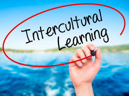 intercultural: Man Hand writing Intercultural Learning with black marker on visual screen. Isolated on nature. Business, technology, internet concept. Stock Photo