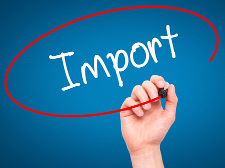 importation: Man Hand writing Import with black marker on visual screen. Isolated on blue. Business, technology, internet concept. Stock Photo