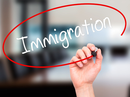 immigrate: Man Hand writing Immigration with black marker on visual screen. Isolated on office. Business, technology, internet concept. Stock Photo Stock Photo