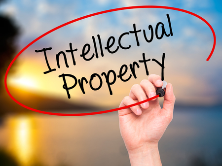 lawer: Man Hand writing Intellectual Property with black marker on visual screen. Isolated on nature. Business, technology, internet concept. Stock Photo