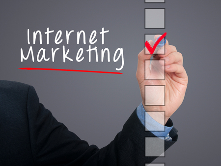 listing: Businessman hand writing Internet Marketing and check listing task. Isolated on grey background. Stock photo