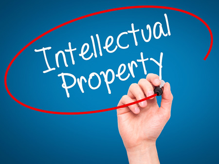 lawer: Man Hand writing Intellectual Property with black marker on visual screen. Isolated on blue. Business, technology, internet concept. Stock Photo Stock Photo