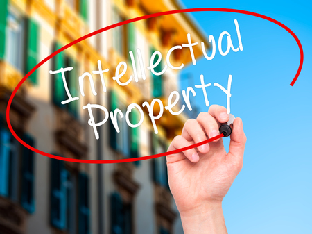 lawer: Man Hand writing Intellectual Property with black marker on visual screen. Isolated on city. Business, technology, internet concept. Stock Photo