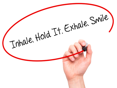 artistic addiction: Man Hand writing Inhale Hold It Exhale Smile with black marker on visual screen. Isolated on white. Business, technology, internet concept. Stock Photo