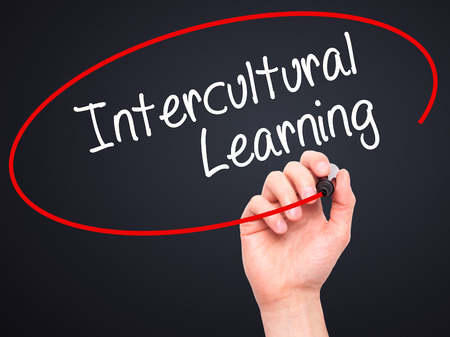 intercultural: Man Hand writing Intercultural Learning with black marker on visual screen. Isolated on black. Business, technology, internet concept. Stock Photo