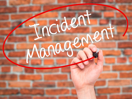 Man Hand writing Incident Management with black marker on visual screen. Isolated on bricks. Business, technology, internet concept. Stock Photo