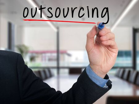 business process: Businessman hand writing Outsourcing isolated on office background. Business concept.Stock Photo