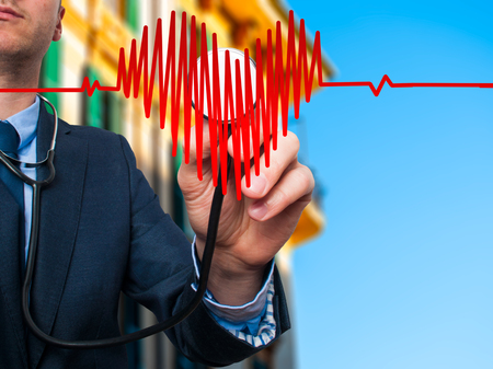 preventive medicine: Closeup portrait handsome business man, male corporate employee, worker listening to  heart with stethoscope isolated on city background. Preventive medicine, financial condition check-up concept