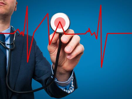 preventive medicine: Closeup portrait handsome business man, male corporate employee, worker listening to  heart beat with stethoscope isolated on blue background. Preventive medicine, financial condition concept Stock Photo