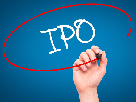 public offering: Man Hand writing IPO (Initial Public Offering)   with black marker on visual screen. Isolated on background. Business, technology, internet concept. Stock Photo