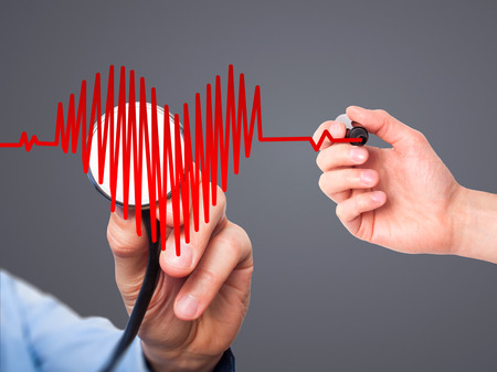 preventive medicine: Closeup portrait doctor hand listening to heart beat in heart shape with stethoscope isolated on grey background. Preventive medicine concept Stock Photo
