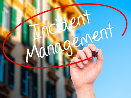 iscp: Man Hand writing Incident Management with black marker on visual screen. Isolated on city. Business, technology, internet concept. Stock Photo