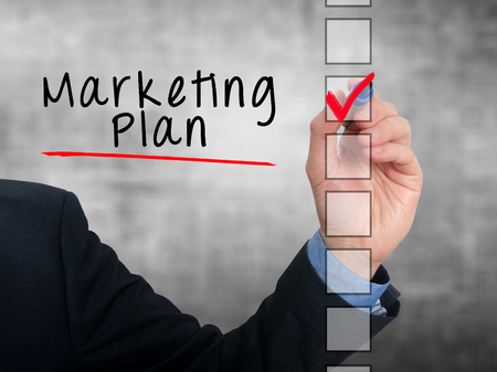stock listing: Businessman hand writing Marketing Plan and check listing task. Isolated on grey background. Stock photo