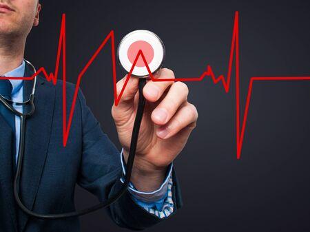 preventive medicine: Closeup portrait handsome business man, male corporate employee, worker listening to  heart beat with stethoscope isolated on black background. Preventive medicine, financial condition concept