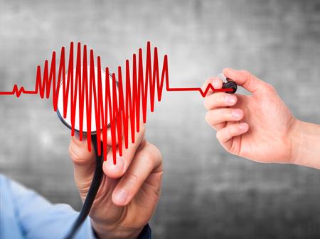 灰色の背景に分離された聴診器で心臓の形でクローズ アップ肖像画医師手の心に耳を傾けを破った。予防医学の概念