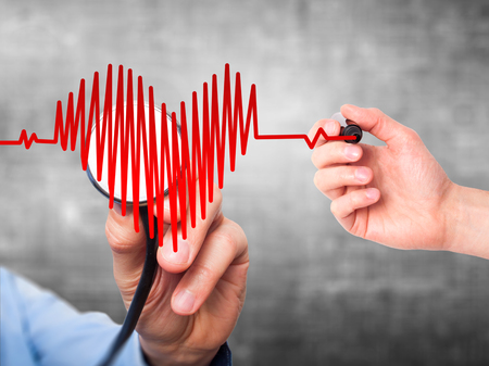 Closeup portrait doctor hand listening to heart beat in heart shape with stethoscope isolated on grey background. Preventive medicine concept Standard-Bild