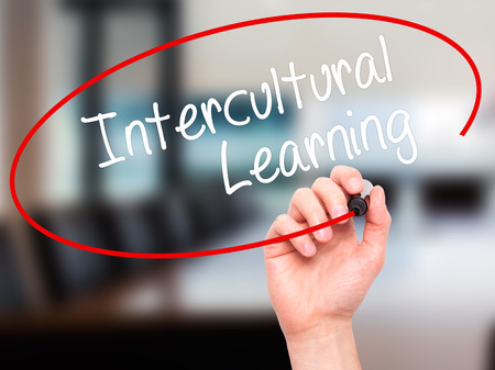 intercultural: Man Hand writing Intercultural Learning with black marker on visual screen. Isolated on office. Business, technology, internet concept. Stock Photo