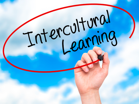 intercultural: Man Hand writing Intercultural Learning with black marker on visual screen. Isolated on sky. Business, technology, internet concept. Stock Photo