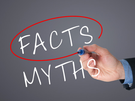 trustworthiness: Businessman hand drawing and choosing Facts instead of Myths. Facts selected with marker. Isolated on grey background. Stock Image