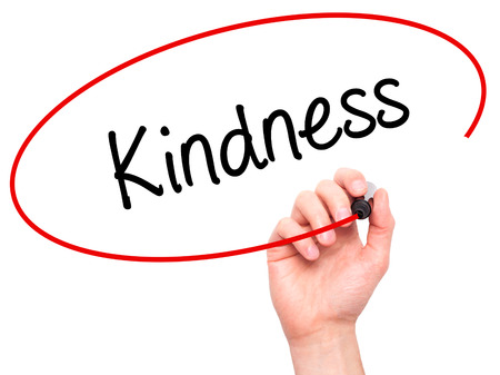 solicitude: Man Hand writing Kindness with black marker on visual screen. Isolated on white. Business, technology, internet concept. Stock Photo