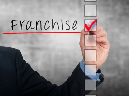 stock listing: Businessman hand writing Franchise and check listing task. Isolated on grey background. Stock photo