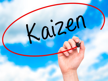 Man Hand writing Kaizen with black marker on visual screen. Isolated on sky. Business, technology, internet concept. Stock Photo Archivio Fotografico